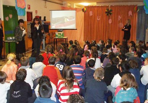 I compagni di classe e gli insegnanti assistono alla consegna del premio ai genitori di Maria.