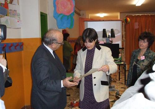 La mamma della bambina premiata riceve la pergamena mentre il premio verrà consegnato direttamente alla bambina a casa sua.