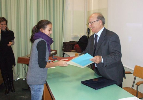 Alla presenza della preside e della direttrice generale, il dott. Pianciamore consegna il premio alla bambina.