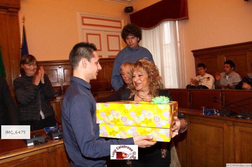 In una grande manifestazione di affetto tutti hanno preparato un dono per Bruno: il Sindaco, i professori e i compagni di classe. La prof.ssa Tina Adamo consegna alcuni regali.