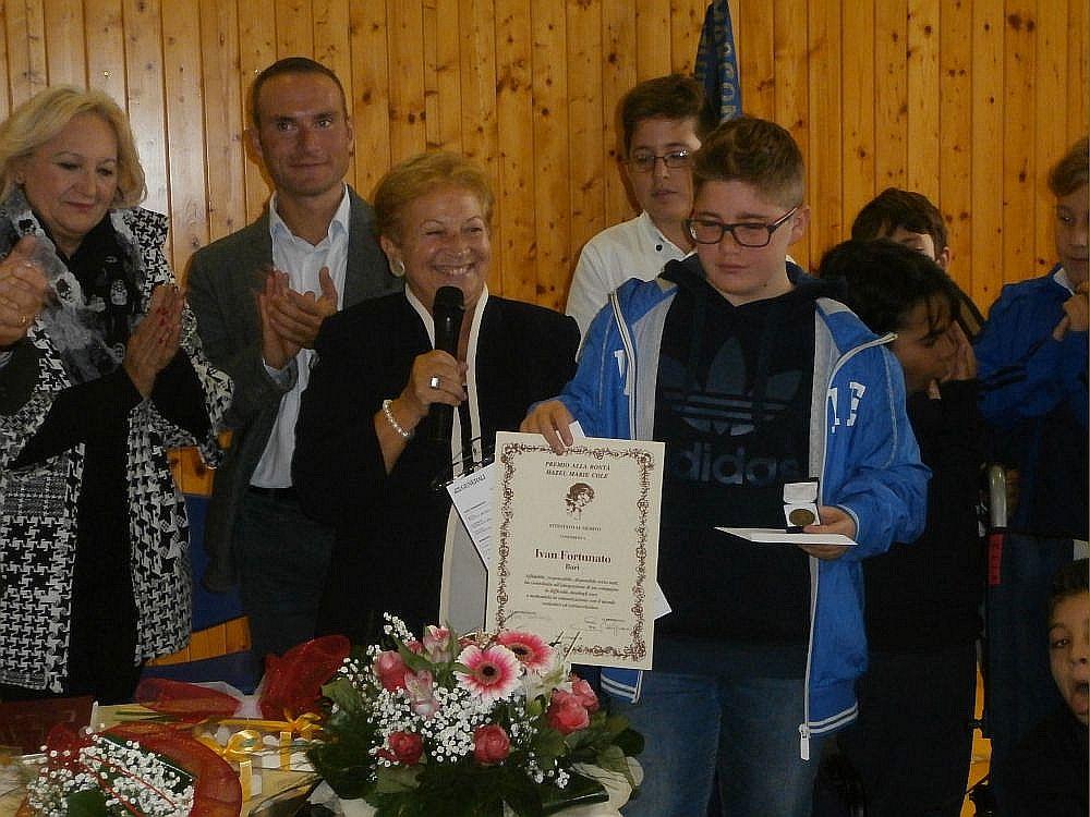 La Prof.ssa Gilda Pianciamore consegna il premio a Ivan, angelo custode di Francesco.