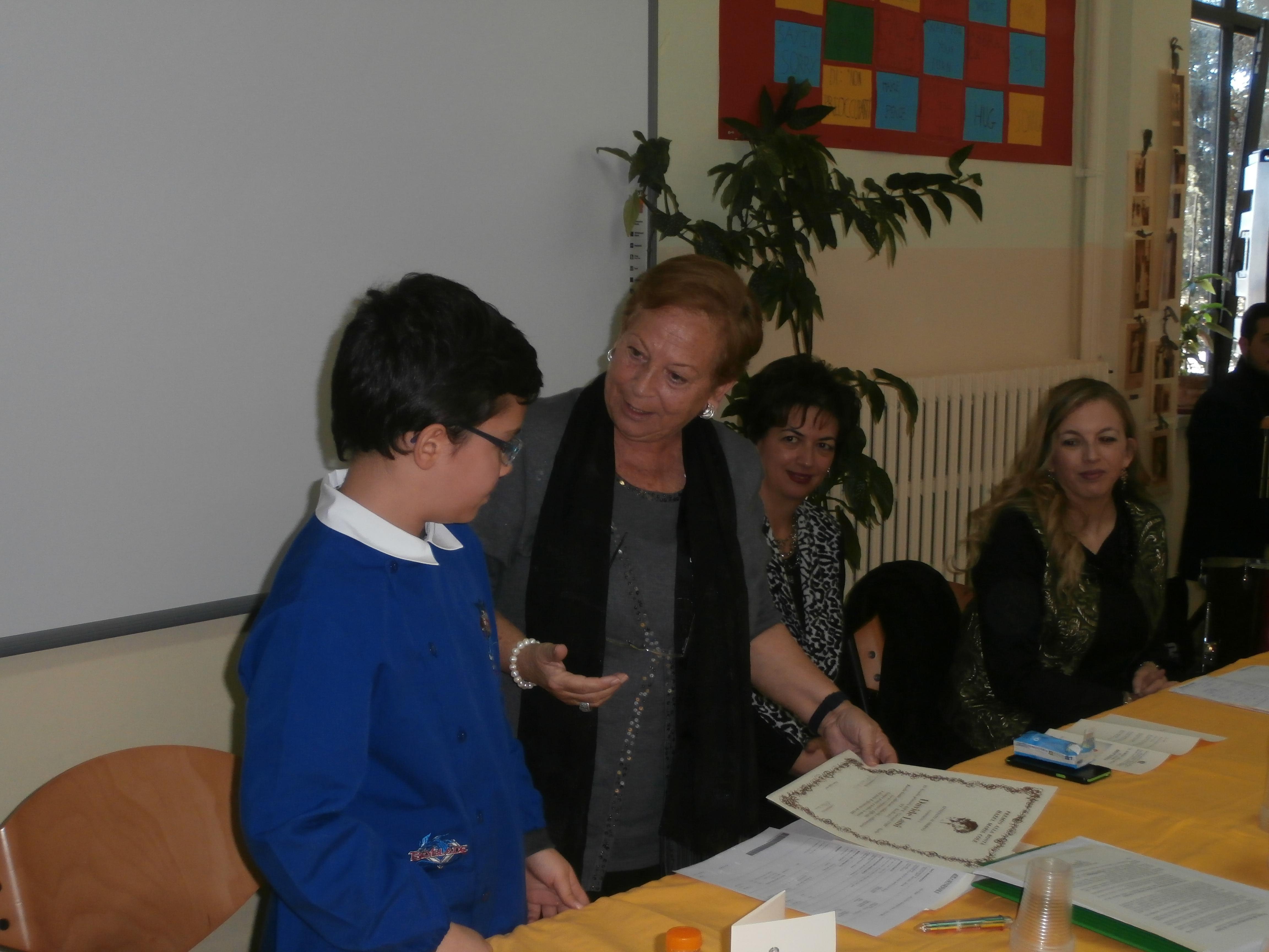 La prof Pianciamore legge la motivazione del premio che poi consegna con gioia a Davide.