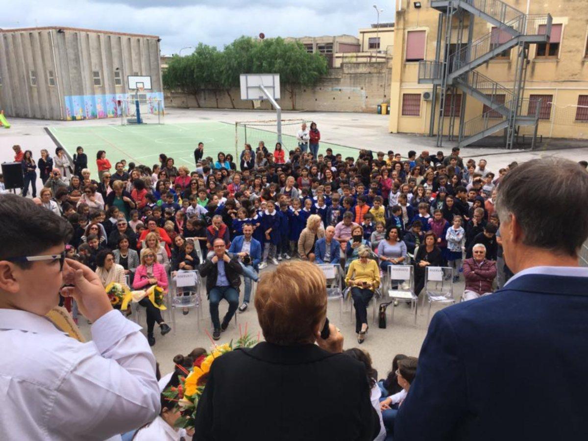 Nel cortile, festosi, I ragazzi insieme ai docenti,sfidano la pioggia per festeggiare il compagno premiato.