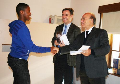 Uno studente mentre ritira l'assegnazione del premio dal dott. Pianciamore