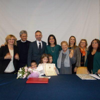 Vittoria mostra con orgoglio la pergamena circondata dall'affetto della famiglia e delle insegnanti.